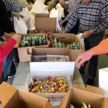Volunteers stuff 600 treat bags for Santa to distribute after the Christmas parade.