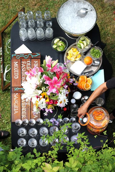 Portable bar set-up at an event with glassware, condiments, and flowers.