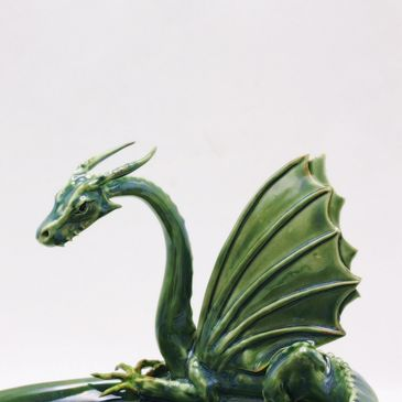 Dragon Spire Ceramics photo featurng a ceramic green dragon sculpture perched on a ceramic bowl.