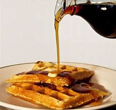 Pouring pure maple syrup over a stack of waffles, one of the many reasons to choose Wisconsin pure maple syrup