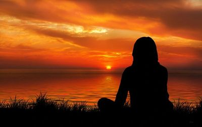 A woman gazes at the sunset in seated meditation