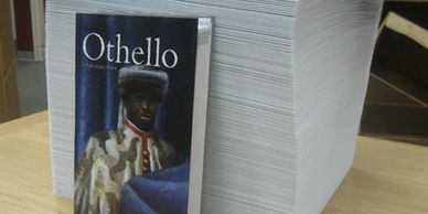 Othello print book in front of Braille book version. Linked to Preferred Braille Network page
