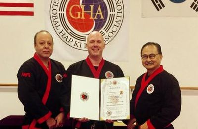 Grand Master Juan Rangel and Grand Master Hee Kwan Lee presenting Master Brown with his 6th Dan