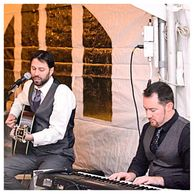 Grades Of Absolute Truth performing with an acoustic guitar with Double J on keys during a wedding