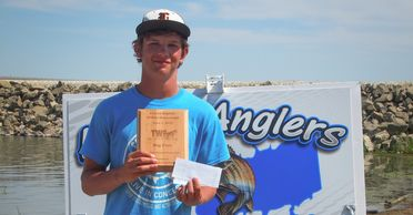 Teen boy holding Big Fish plaque in front of Harlan Anglers Banner