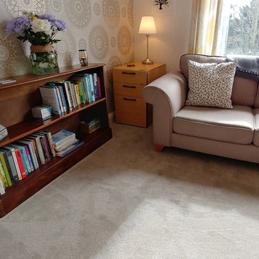 An image of the therapy room, showing a sofa and a bookcase.