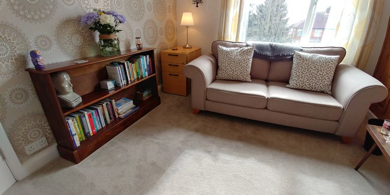 A bright airy therapy room with a light coloured sofa on the right, and a bookcase on the left.