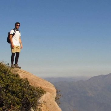 Chilean CMO, Flavio Rondalli, hiking near the edge of a cliff with a beautiful view.