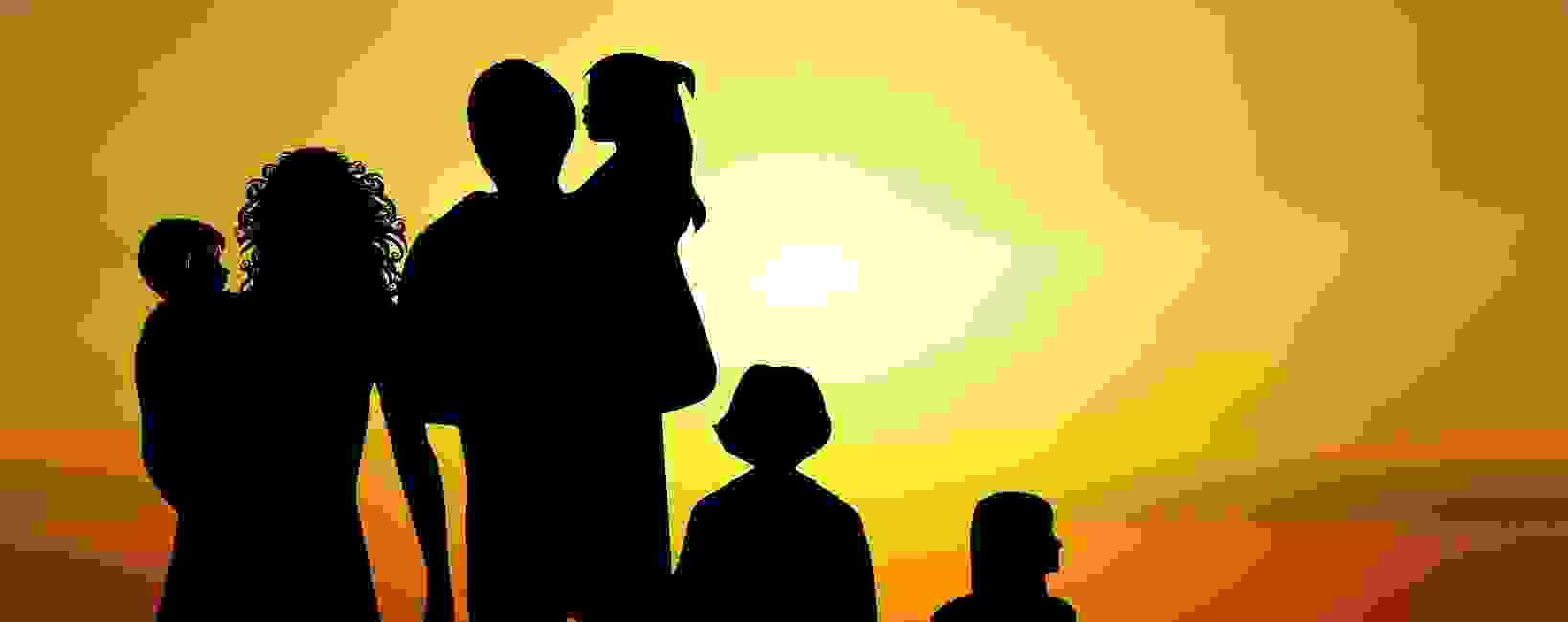 Silhouette of a family on the beach looking out over a sunset, signifying hope and optimism.