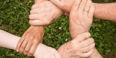 Five hands clasping each otherat the wrist to show unity and connection.