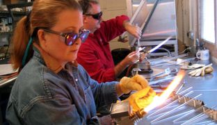 Participants learning Glass Beadmaking at a fundraising event benefitting Children's Hospital.