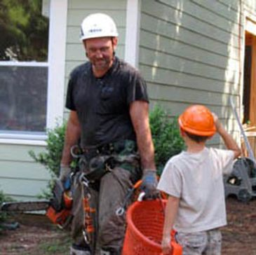 Tree professional in tree removal gear with saw talking to young customer