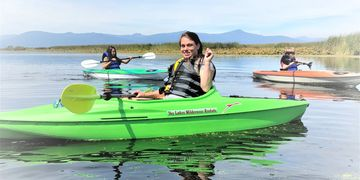 Kayak Rentals on the Wood River Wetlands with Sky Lake Wilderness mountain range in the background.
