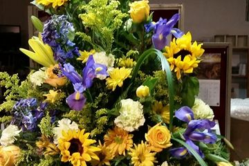 Metal Container, Sunflowers, Blue Iris, Orange Roses. Lite Yellow Carnations, And $175.00