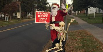 "Santa and Mr. Bonejangles (Skeleton) with a ""Blood Drive Today"" sign"
