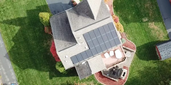 Residential rooftop solar array on the back roof of a home. Photographed with a drone