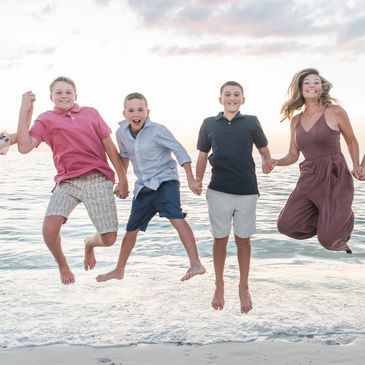 Kids holding hands and jumping above the ocean - Portrait by Alma B Photography