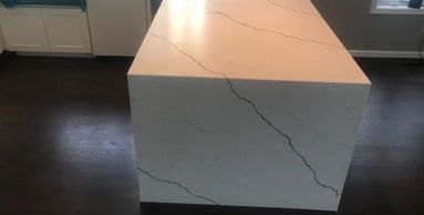 Pental Quartz Arezzo Honed with Farm Sink and Custom miter waterfall edge to floor.
