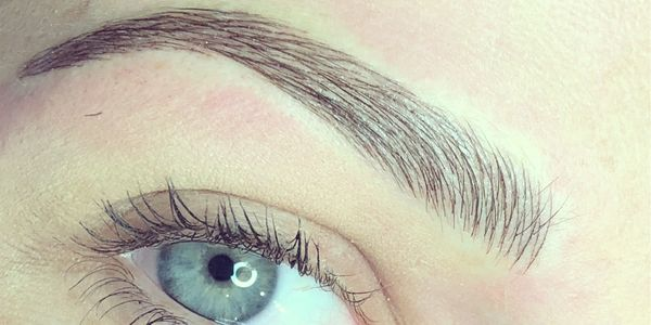 picture of microblading on an eyebrow on a face with blue eyes,