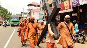 Carrying a large cross but wearing Hindu monks attire. WHY?