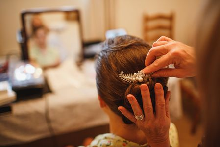 Finishing touches to a Arie messy Chignon or bun at the back of a brides wedding hair in Cheshire