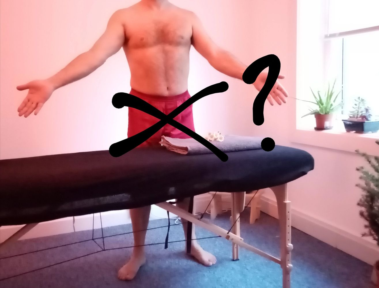 James at SkinMap, in front of massage table   the implication that his shorts are optional