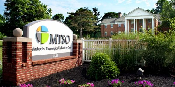 MTSO entrance: sign, blooming purple flowers, & red brick building with columns (Dickhaut Library)
