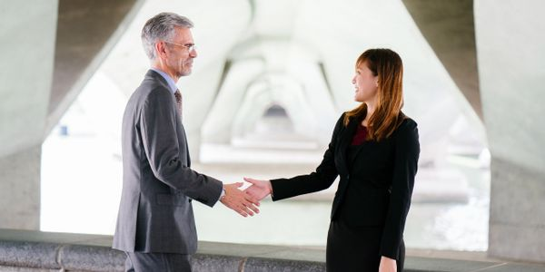 Man and woman shaking hands in a business environment