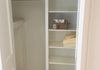 Custom linen closet next to tub also houses audio equipment for shower stereo