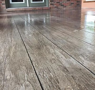 Stamped overlay concrete wood floor finish with gray and charcoal tones.