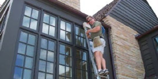 window cleaner on ladder cleaning french window panes