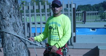 Delfino in yellow shirt Aldine tree services Houston stump grinding. Safety harness in Sugar Land