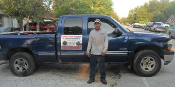 Man in gray shirt standing next to blue truck with sign reading Aldine Tree Service Free Estimates