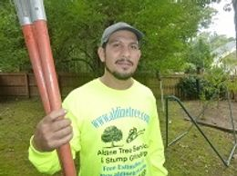 Delfino Sanchez holding pole saw in yellow shirt reading Aldine tree services Houston stump grinding