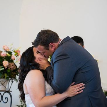 A beautiful moment captured on a special day; a groom kisses his new wife for the first time.