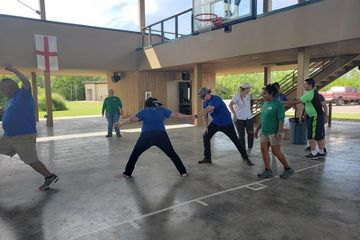 A group of adults participating in a team building exercise.