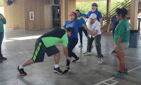 Adults participating in a team building exercise at camp.