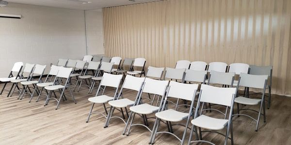 Three rows of white fold-up chairs inside a meeting room.