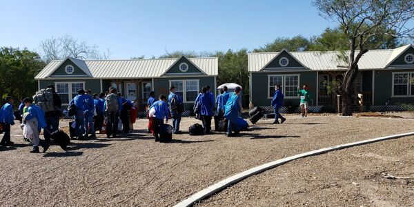 A group of school children walking towards summer camp cabins with their luggage.
