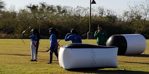 A group of school children playing archery tag in an open field.