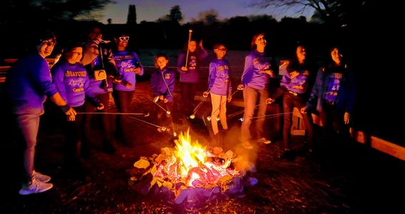 A group of school children and teachers roasting marshmallows on a campfire.