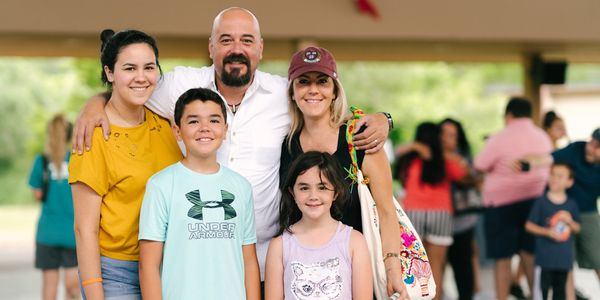 A family posing for a photo at summer camp pick up day.