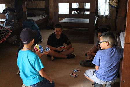 Summer camp kids playing cards on cabin floor