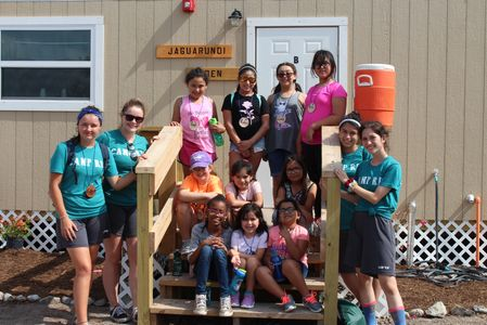 Camp counselors pose with summer camp kids in front of cabin.