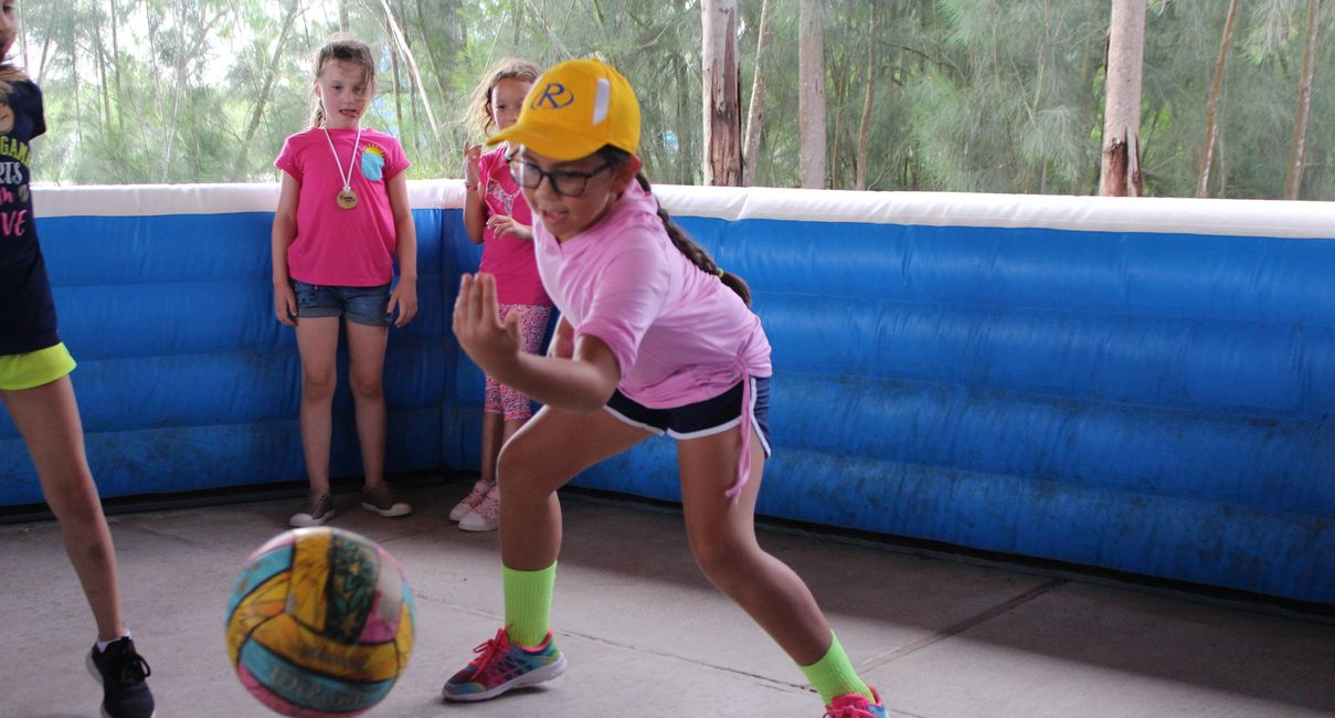 Girl playing with ball at summer camp.