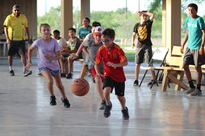 A group of summer camp children playing basketball in an outdoor pavilion.