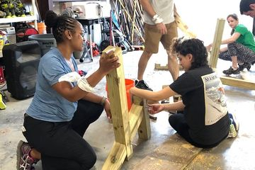 A group of adults building a bench made from wood.