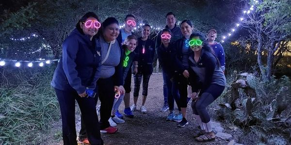 Adults wearing glow glasses at camp next to outdoor string lights.