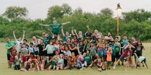 A group of summer camp staff and children posing for a photo in a field.