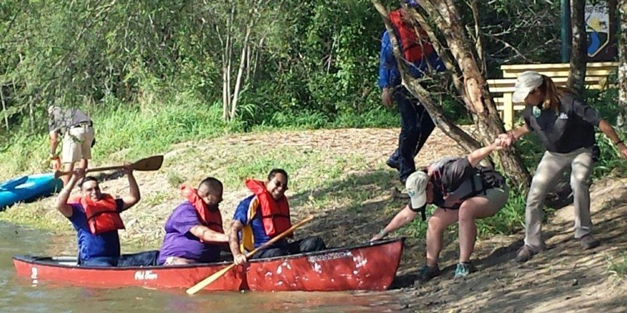 A group of adults participating in a team building exercise with canoeing.
